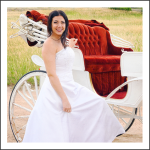Lovely bride standing next to a white carriage with red velvet seating interior, being pulled by two white horses.