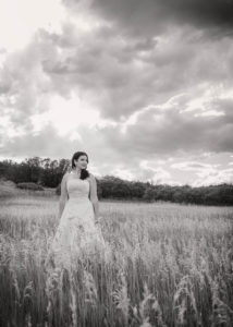 Lovely bride standing in a wheat field black and white