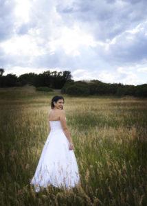 Lovely bride standing in a wheat field