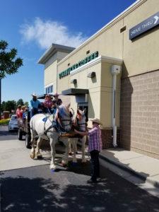 horse drawn carriage going through a Starbucks drivethrough