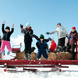 a crowd of children jumping off of a red carriage into a large compiled snow heap.