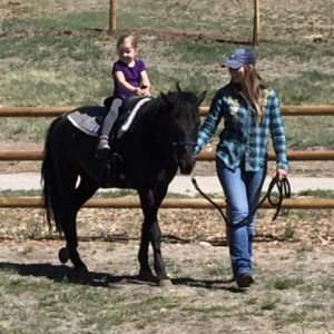 a mother pulling a pony with a child riding.