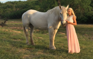 a young princess standing next to her white horse
