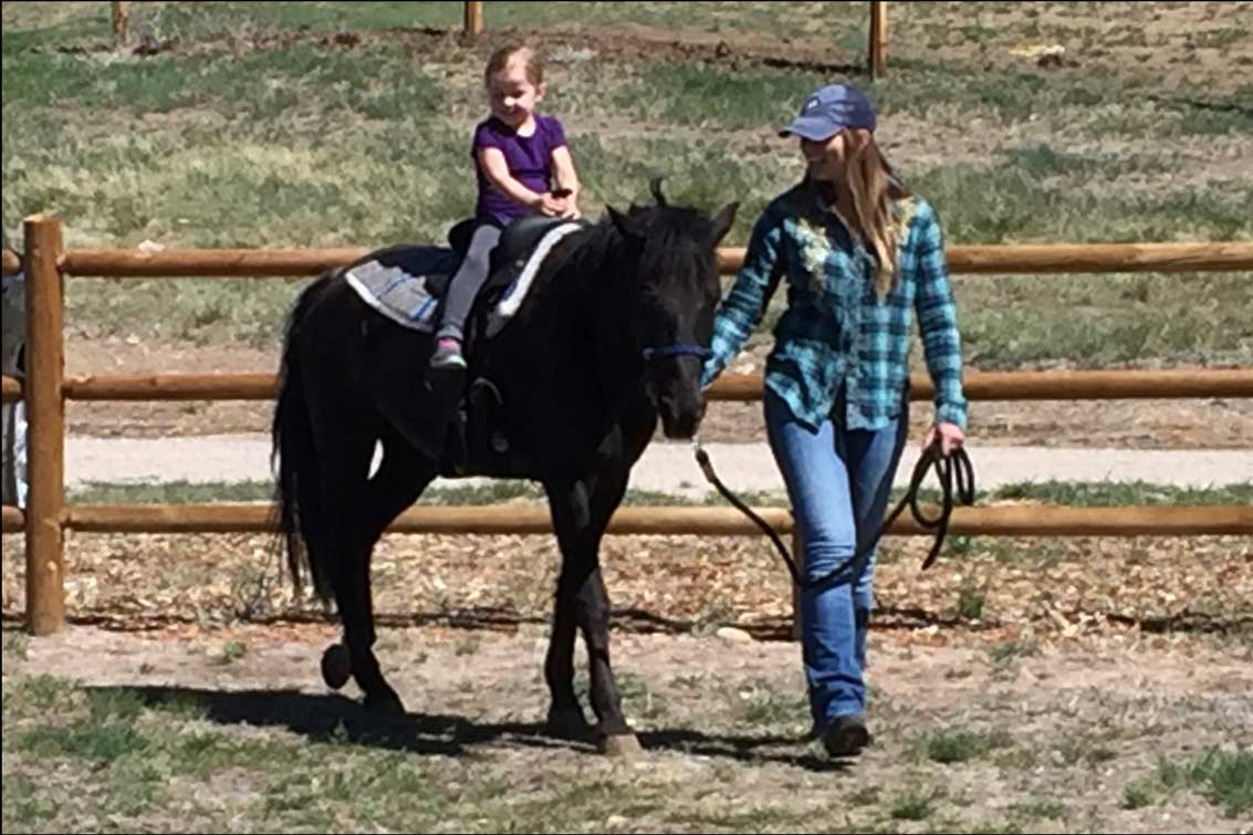 Young girl being led on a pony by an adult.
