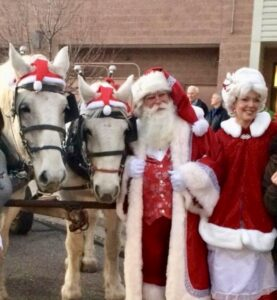 Two old folks dressing up as Mr and Mrs Santa Clause